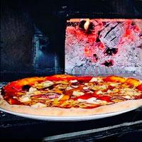 deliciosa pizza galleto con horno de leña detrás