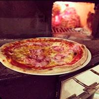 deliciosa pizza prosciutto con fuego de horno de leña detrás