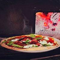 pizza tartufata con fuego de horno de leña detrás